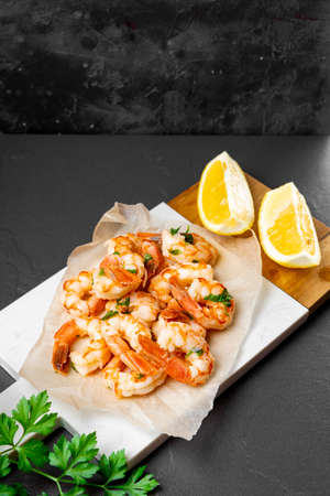 Fried shrimps with lemon on a cutting board, vertical photo with copyspace