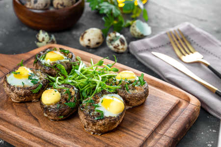 Baked champignons with quail eggs and microgreen garnish on a wooden cutting board close up