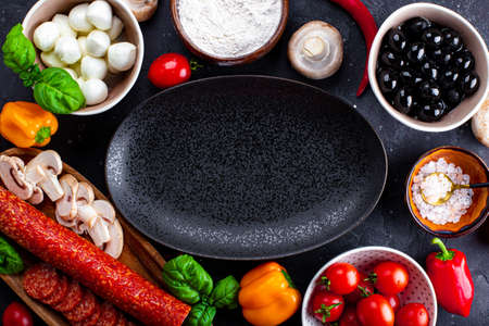 Pizza ingredients on the dark background and black plate. Pepperoni sausage, mozzarella cheese, tomatoes, olives, mushrooms and flour are different products for making pizza and pasta Stockfoto