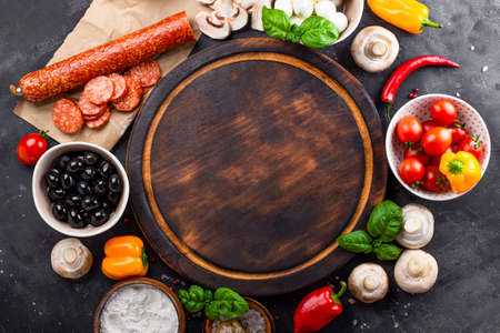Pizza ingredients on the dark background and round cutting board, free space for text. Pepperoni, mozzarella, tomatoes, olives, mushrooms and flour are different products for making pizza and pasta