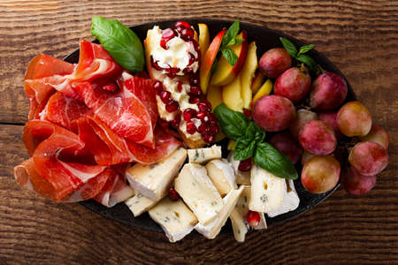 A set of appetizers for wine, jamon, pepperoni, cheese, grapes, peach on a plate top view. Snack board on wooden background, close up