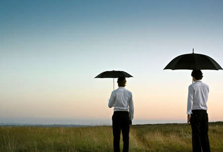 Two men with a black umbrella in an open, green field  Stock Photo
