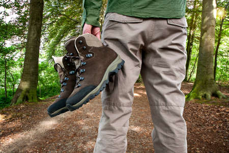 Man holding hiking shoes, in the woods  Stock Photo