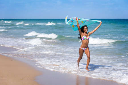 Young woman at the beach with a colored sarong, walking in the water.