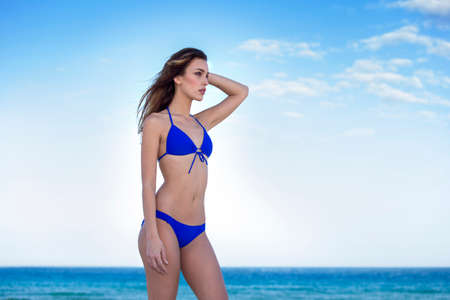 Woman in blue bikini, at the beach. Looking away. Stock Photo