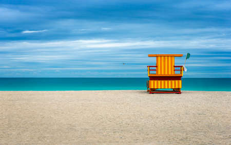 guard house: Colorful Life Guard house on an empty beach, cloudy blue sky. Stock Photo