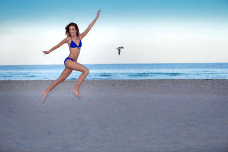 Young cheerful woman in bikini jumping on the beach.