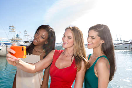 Portrait of three women taking selfies with a smartphone. Three friends posing for selfie, outdoors. Stock Photo