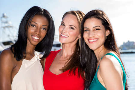 Three women posing in marina harbor, yachts on background. Stock Photo