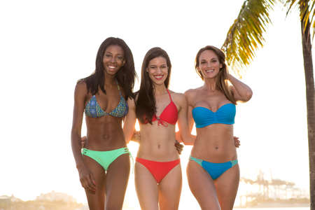 Three women in bikini walking, back lit.