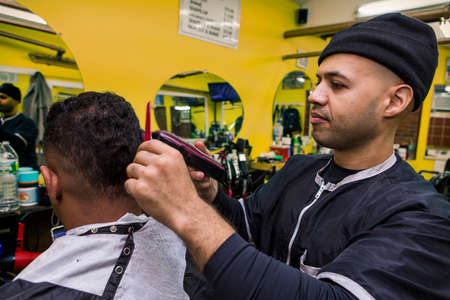 Barber Giving his client a Haircut, In Barber Shop Stock Photo