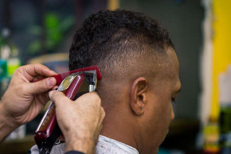 Barber trims hair or client, close up.