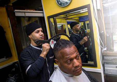 Barber shows short haircut with mirror to happy client in a barber shop.