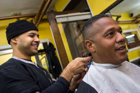 Barber Giving his client a Haircut, In Barber Shop Standard-Bild