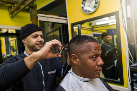 Barber Giving his client a Haircut, In Barber Shop Stock fotó
