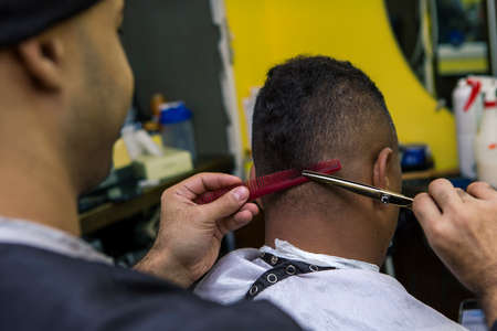 trims: Barber trims hair or client, close up.