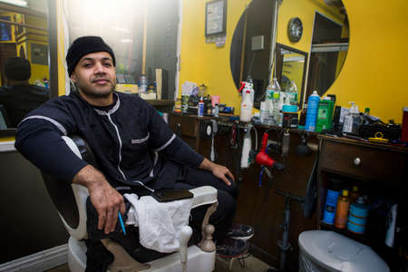 Barber posing in his shop.