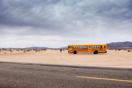 motorcoach: 29 Palms, CaliforniaUSA-03212016: School Bus in the desert, 29 palms,  Boy is walking towards the horizon.