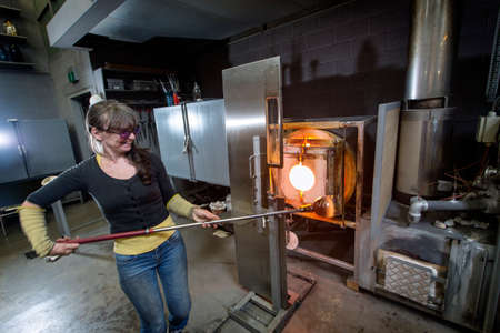 emale glass artist, working in a workshop, shaping a vase.