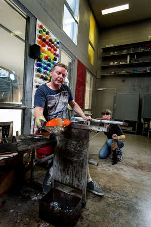 Glass artist, working on a vase. Handmade.