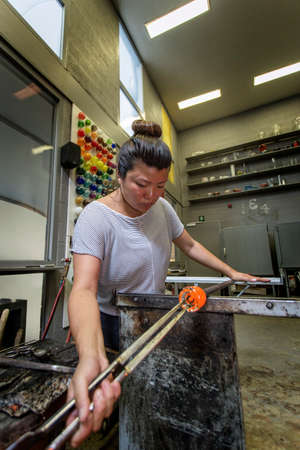 Female glass artist, working in a workshop, shaping a vase. Stock fotó