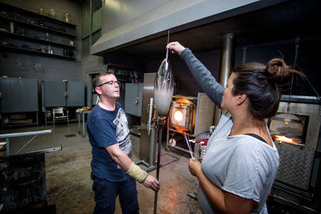 Glass artists, working on a vase.