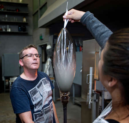 Glass artists, working on a vase. Handmade.