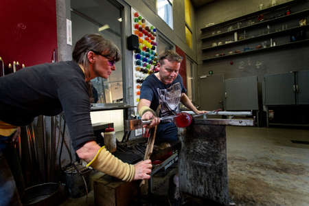 Glass artists, working on a vase. Handmade