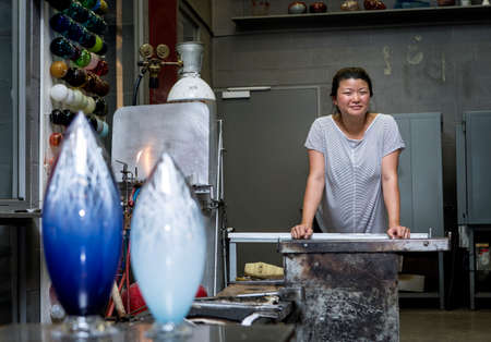 Female glass artist, posing in a workshop, showing vases. Stock fotó