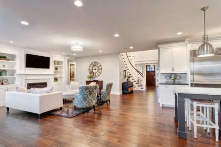 family in living room: Beautiful living room in luxury home with view of kitchen and entry