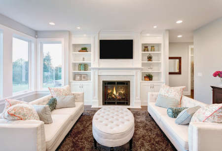 family in living room: Beautiful Living Room with Fireplace in New Luxury Home