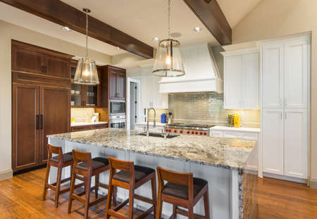 Kitchen interior with hardwood floors in new luxury home: island, pendant lights, cabinetry, and range with hood. Stock Photo