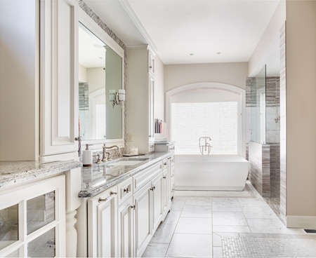 bathroom mirror: Bathroom interior in luxury home, focus on cabinetry and sink with mirror. Bathtub and shower in background