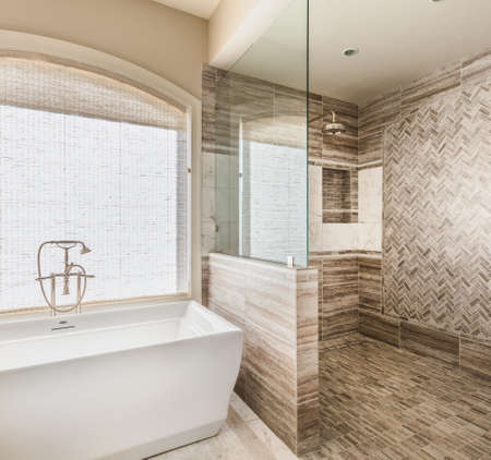 bathroom tiles: Bathtub and shower in new luxury home