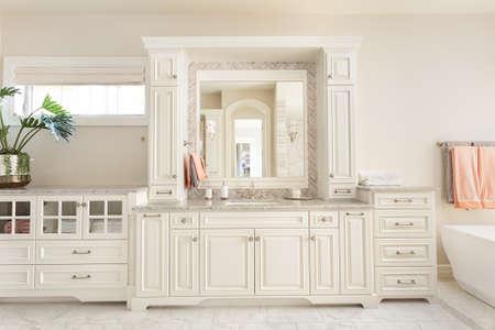 Badkamer interieur in nieuwe luxe huis: ijdelheid, wastafel en spiegel, met een deel van het bad