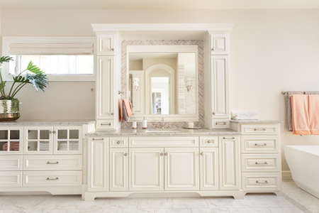 Bathroom interior in new luxury  home: vanity, sink, and mirror, with part of bathtub Stock Photo