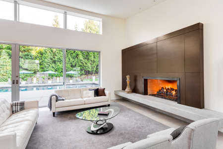 Beautiful living room in luxury home with fireplace, tv, couches, and glimpse of backyard patio