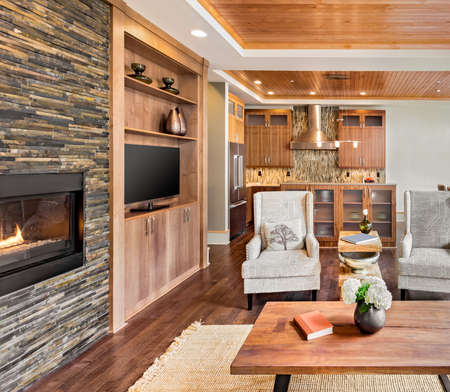 wood ceiling: living room interior in luxury home with wood strip ceiling, fireplace with fire, and view of kitchen