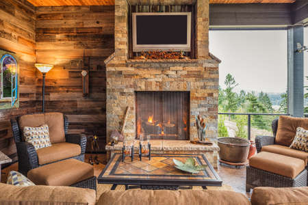 Covered Outdoor Patio Outside New Home with Couch, Chairs, TV, Fireplace, and Roaring Fire Foto de archivo