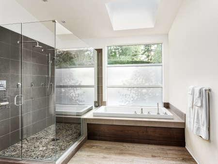 Intérieur de bain dans la nouvelle maison de luxe: une baignoire avec douche à l'italienne de carreaux curbless, avec tout porte en verre et les murs. Banque d'images - 46487567