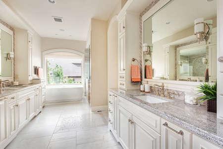cuarto de baño: Gran cuarto de baño interior en hogar de lujo con dos lavabos, pisos de cerámica, gabinetes de lujo, grandes espejos y bañera