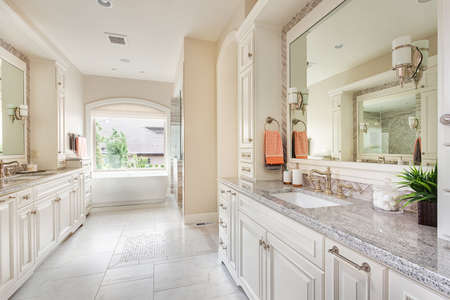 bathroom mirror: Large bathroom interior in luxury home with two sinks, tile floors, fancy cabinets, large mirrors, and bathtub
