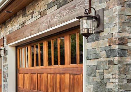 ガレージ詳細をホーム: ガレージのドア、壁取り付け用燭台の光と石積み 写真素材