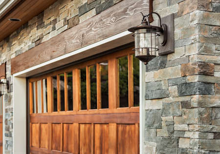 architectural exterior: Home garage detail: garage door, sconce light, and stonework Stock Photo