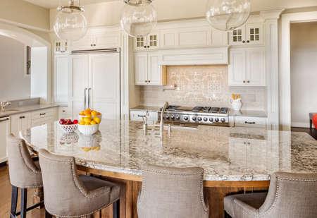 Keuken met kookeiland, gootsteen, kasten en hardhouten vloeren in New Luxury Home