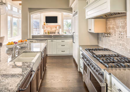 granite kitchen: Kitchen with Range, Sink, and Hardwood Floors in New Luxury Home Stock Photo