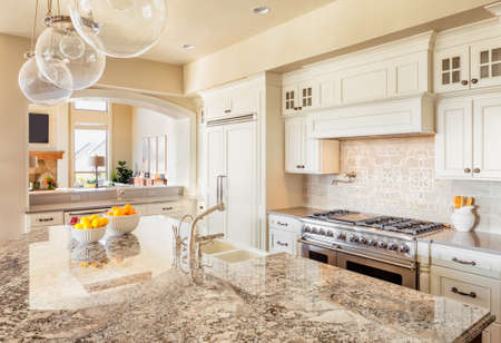 expensive granite: Kitchen with Island, Sink, Cabinets, and Hardwood Floors
