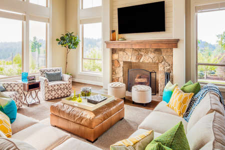 furniture home: Furnished living room in new luxury home with fireplace, ottoman, tv, couches, and colorful cushions