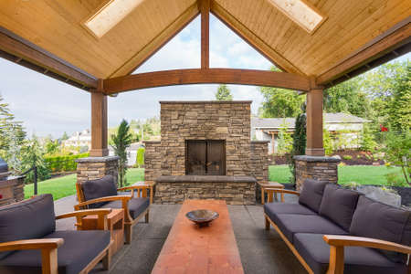 Covered patio outside luxury home with large stone fireplace, table, and couches