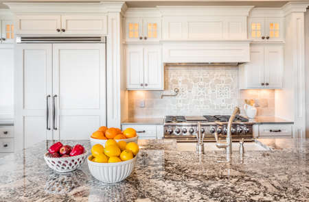 kitchen cabinets: Kitchen Detail in New Luxury Home with Colorful Fruit Stock Photo